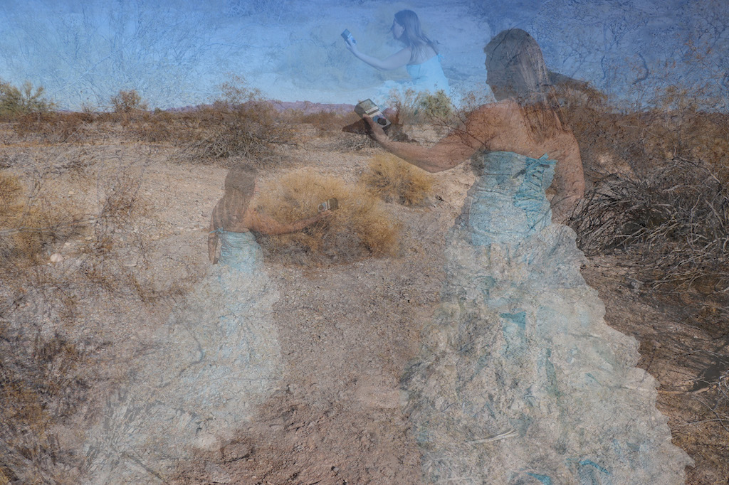The image consists of three photographs superimposed upon each other. All the images of are Marie LeBlanc in a rocky and dry area with scrub bushes and low mountains in the distance with a clear blue sky. All three images of Marie are holding an electronic device (triField meter to measure magnetic, electric and RF) in their hands and are transparent. One image of Marie on the left-hand side is standing and holding the device in her right hand. The image of Marie on the right-hand side of the image is standing and holding the device in her left hand. The final image of Marie is near the top center of the image and she is squatting down with the device in her left hand. Marie is a thin white woman with straight long brown hair and is wearing a blue strapless dress with lots of frills at the bottom.
