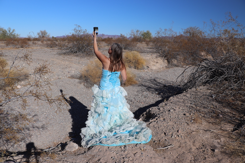 Photograph of Marie LeBlanc standing in a rocky and dry area with lots of scrub bushes and low mountains in the distance. Marie has her back to the viewer and is holding a device in her left hand high up in the air and is looking at it. Marie is a thin white woman with straight long brown hair and is wearing a blue strapless dress with lots of frills at the bottom.