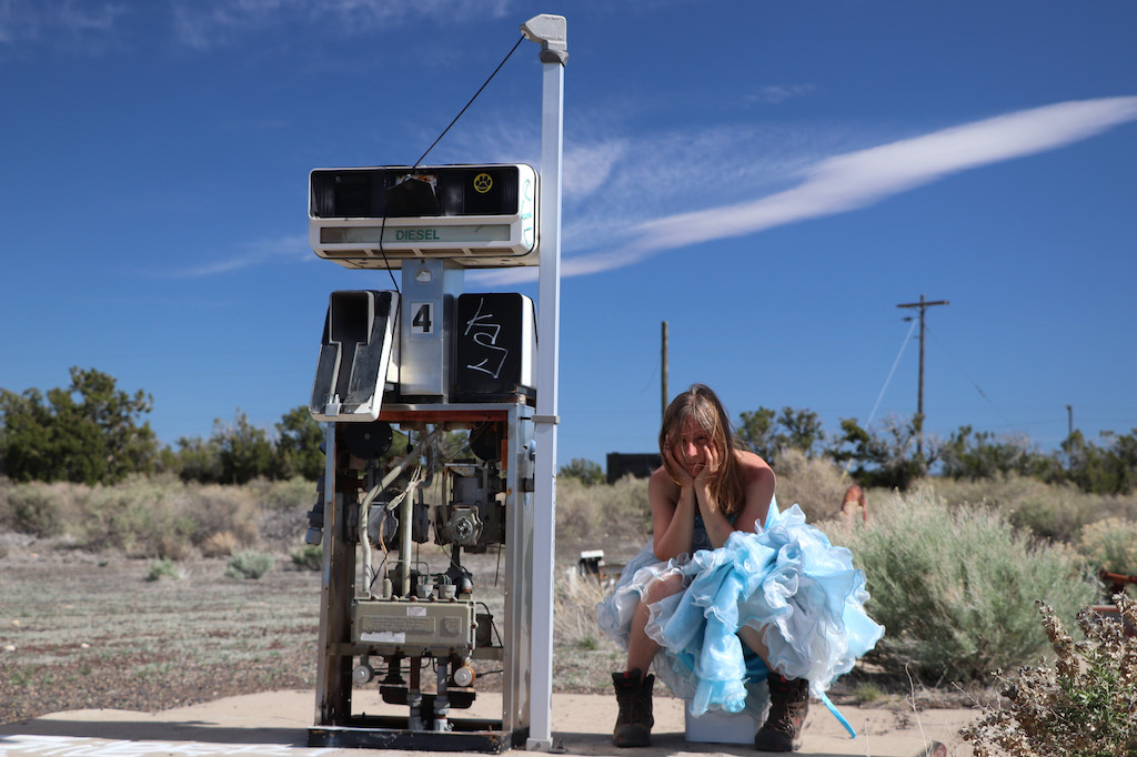 Photograph of Marie LeBlanc sitting on a bucket next to an old gas pump. The area behind Marie is rocky with lots of scrub bushes and short trees in the distance. The sky is bright blue with a few clouds. Marie sits bent over with her head in her hands and is looking directly at the viewer. Marie is a thin white woman with straight long brown hair and is wearing a blue strapless dress with lots of frills at the bottom and work boots.
