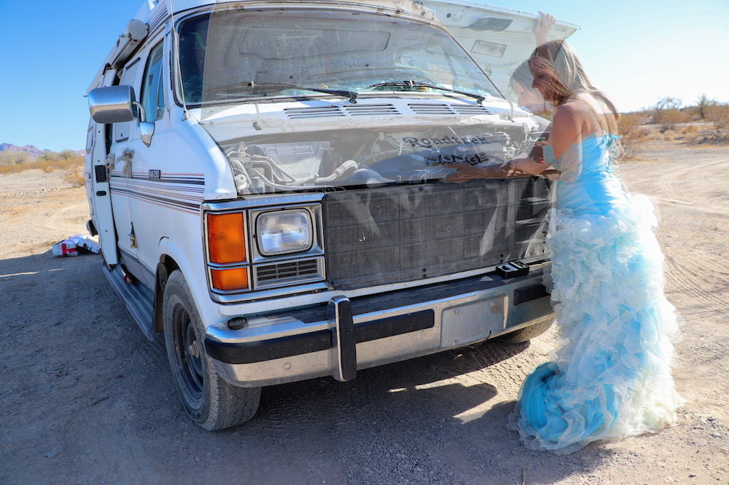 Photograph of Marie LeBlanc standing in front of the hood of her van. The van is parked in a dry area with lots of sand, rocks and scrub bushes. The sky clear blue. There are two images of Marie superimposed into the image. One image of Marie is opening the catch of the van's hood and the other image of Marie is holding up the hood and looking at the motor. Both images are of Marie are transparent. Marie is a thin white woman with straight long brown hair and is wearing a blue strapless dress with lots of frills at the bottom and work boots.