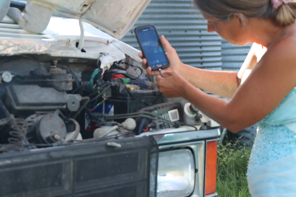 Photograph of Marie LeBlanc plugging her cell phone into a cord that is coming from the open hood of her van. This image is a close up and only Marie's profile and arms can be seen. Marie is a thin white woman with straight brown hair pulled back.