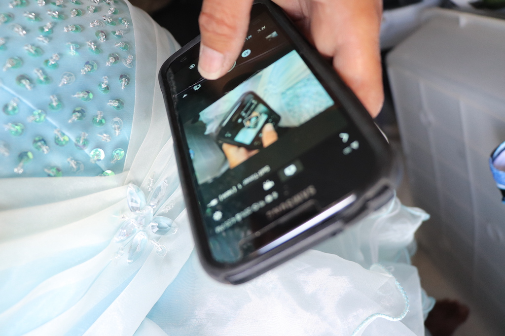 Close up photograph of Marie LeBlanc's cell phone. The image on the cell phone is the same image that the view sees creating a Droste effect (image goes on for infinity). The phone is against Marie's dress with is blue and has beads, crystals and sequence sewn on it.