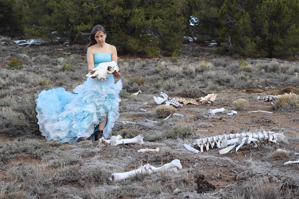 Photograph of Marie LeBlanc in an outdoor area with dry grass and bushes behind her. There are animal bones on the ground and Marie is holding a cow skull in her hands and looking at the viewer. Marie is a thin white woman with straight long brown hair and is wearing a blue strapless dress with lots of frills at the bottom and work boots.