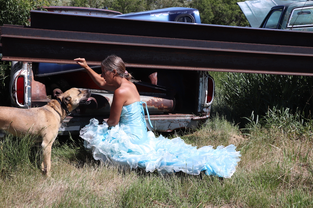 Photograph of Marie LeBlanc kneeling down next to a metal beam and two old broken down trucks behind her. The area that Marie is in is grassy with trees behind the trucks. There is a happy dog on Marie's left side looking up at her. Marie is a thin white woman with straight long brown hair and is wearing a blue strapless dress with lots of frills at the bottom.