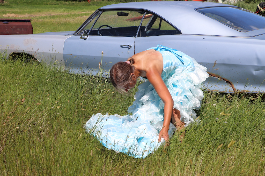 Photograph of Marie LeBlanc in a grassy field with an old car parked behind her. Marie is bent over and looking down at the train of her fancy dress. Marie is a thin white woman with straight long brown hair and is wearing a blue strapless dress with lots of frills at the bottom.