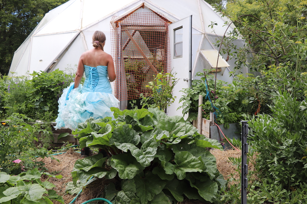 Photograph of Marie LeBlanc from behind in front of a geo dome green house. Where Marie is standing is a lush garden and there are trees behind and beside the geo dome. Marie is a thin white woman with straight long brown hair and is wearing a blue strapless dress with lots of frills at the bottom.