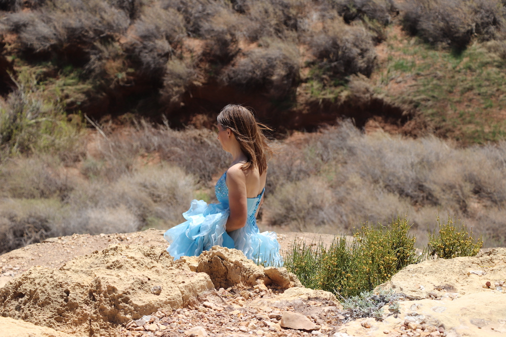 Photograph of Marie LeBlanc in profile, walking down a rocky hill with yellow flowers with green leaves beside her. The terrain in the background is rocky with scrub bushes. Marie is a thin white woman with straight long brown hair and is wearing a blue strapless dress with lots of frills at the bottom which she is carrying in her arms.