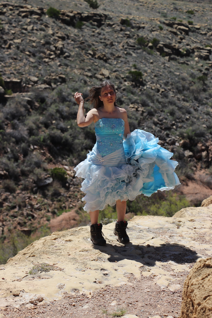 Photograph of Marie LeBlanc standing on a rock cliff. Behind her is a rocky hill with scrub bushes and dry grass. Marie is a thin white woman with straight long brown hair and is wearing a blue strapless dress with lots of frills at the bottom which she is holding in her hand and work boots.