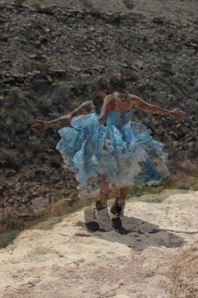 Photograph of Marie LeBlanc standing on a rock cliff. Behind her is a rocky hill with scrub bushes and dry grass. There are two transparent images of Marie superimposed in the image. Marie is a thin white woman with straight long brown hair and is wearing a blue strapless dress with lots of frills at the bottom which she is holding in her hand and work boots.