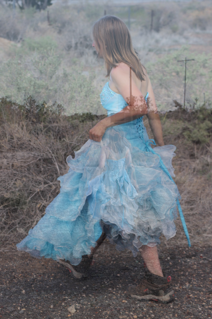 2 photographs superimposed upon the other. One image is a full body shot of Marie LeBlanc walking outside along a dirt road. The second image is a far-shot of Marie walking along a dirt path. The terrain looks rocky and has scrub bush and trees. Marie is a thin white woman with straight long brown hair and is wearing a blue strapless dress with lots of frills at the bottom which she is holding in her hand and work boots.