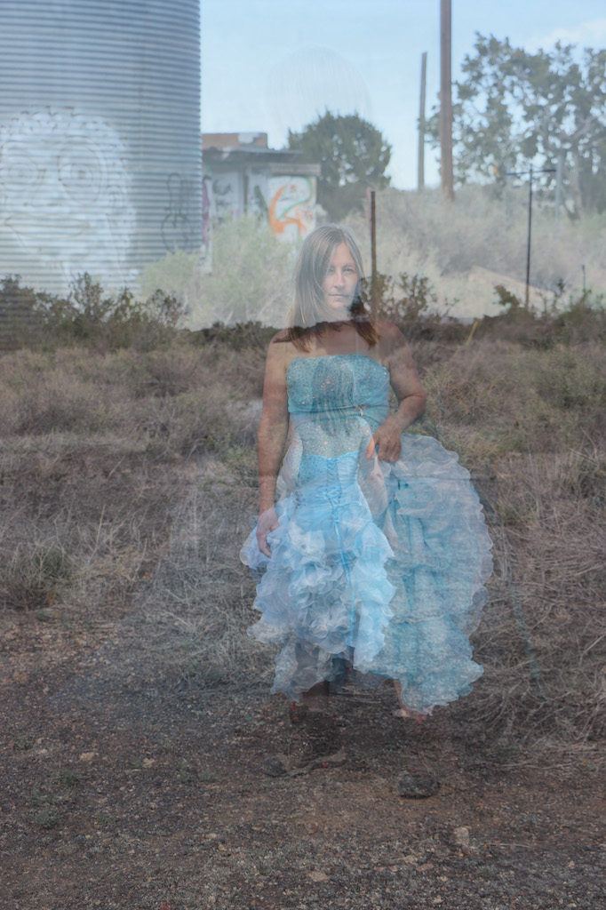 2 photos of Marie LeBlanc standing on a rocky ground with scrub bushes in front of a metal building and a smaller brick building with graffiti over both. There are trees in the background and telephone poles. The first image of Marie is transparent and is a full body shot with her looking directly at the viewer with a slight smile. The second image of Marie is also transparent and she is further away and viewed from behind. Marie is a thin white woman with straight long brown hair and is wearing a blue strapless dress with lots of frills at the bottom which she is holding in her hand and work boots.