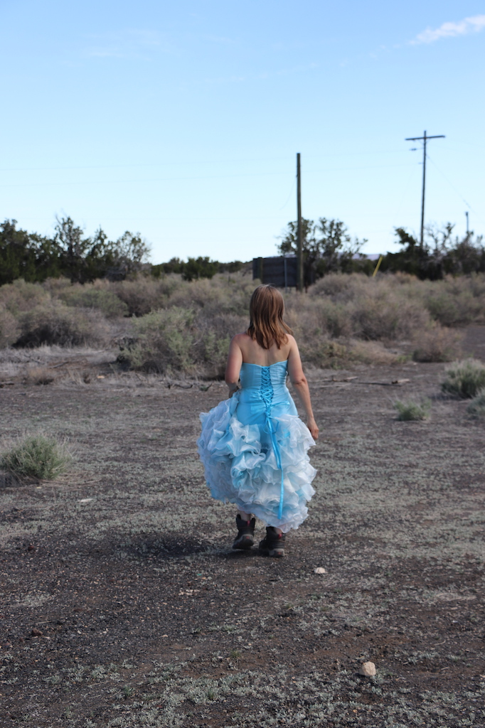 Photograph of Marie LeBlanc walking away on a rocky terrain with scrub bushes and trees in the distance. There are three telephone poles and the sky is a clear blue. Marie is a thin white woman with straight long brown hair and is wearing a blue strapless dress with lots of frills at the bottom which she is holding in her hand and work boots.