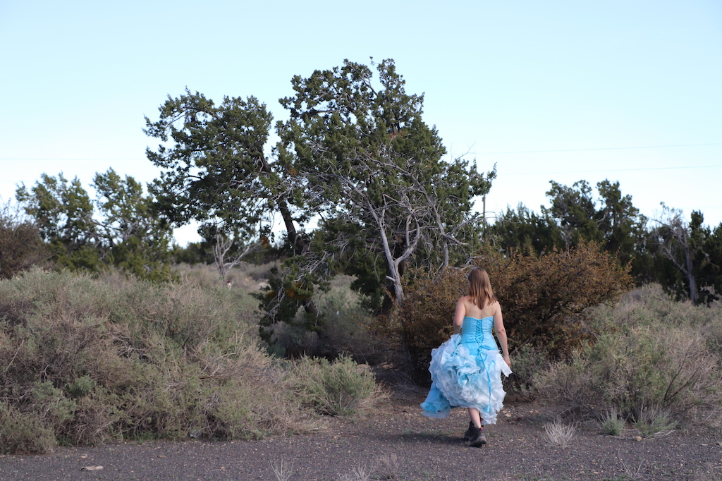 Photograph of Marie LeBlanc walking down a path that leads from an open rocky area to a brush filled area with tress. The sky is a light blue fading to white at the horizon. Marie is a thin white woman with straight long brown hair and is wearing a blue strapless dress with lots of frills at the bottom which she is holding in her hand and work boots.