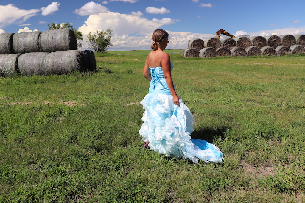 Photograph of Marie LeBlanc standing in profile with her back to the viewer. Marie is in a grassy field with haybales in the upper left and right of the image. Two trees can be seen on the left and part of some farming equipment can be seen behind the haybales on the right. The sky is blue with lots of white clouds. Marie is a thin white woman with straight long brown hair and is wearing a blue strapless dress with lots of frills at the bottom which she is holding in her hand and work boots.