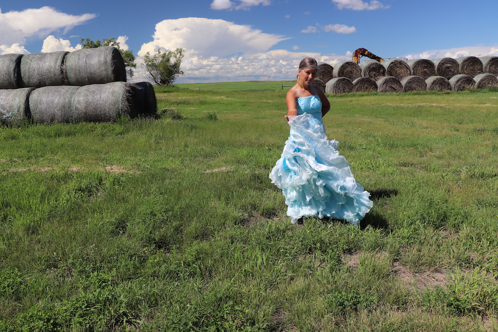 Photograph of Marie LeBlanc standing in looking at the viewer with one hand stretched out in invitation and the other behind her back. Marie is in a grassy field with haybales in the upper left and right of the image. Two trees can be seen on the left and part of some farming equipment can be seen behind the haybales on the right. The sky is blue with lots of white clouds. Marie is a thin white woman with straight long brown hair and is wearing a blue strapless dress with lots of frills at the bottom.