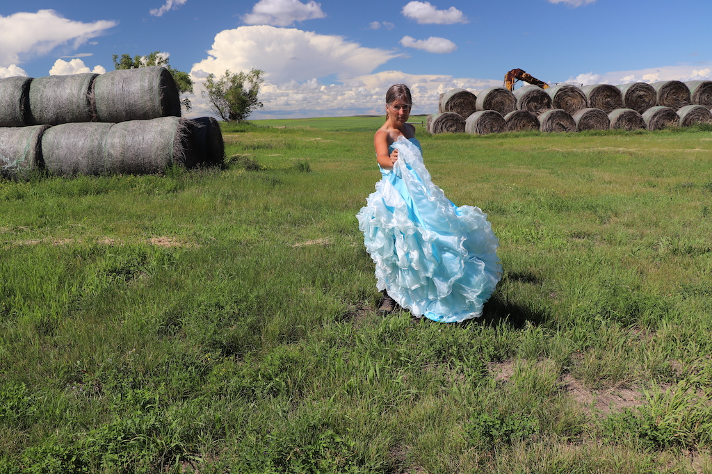 Photograph of Marie LeBlanc standing in looking at the viewer holding the bottom of her dress up so that all the layers of frills are visible. Marie is in a grassy field with haybales in the upper left and right of the image. Two trees can be seen on the left and part of some farming equipment can be seen behind the haybales on the right. The sky is blue with lots of white clouds. Marie is a thin white woman with straight long brown hair and is wearing a blue strapless dress with lots of frills at the bottom.