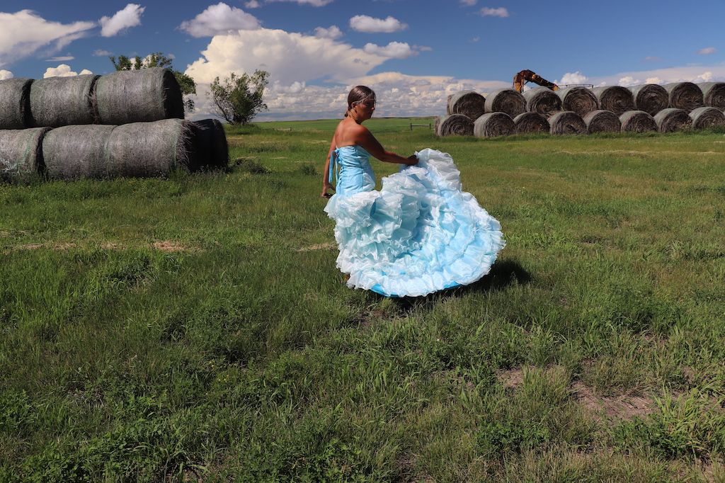 Photograph of Marie LeBlanc dancing and holding the bottom of her dress so that all the layers of frills are visible. Marie is in a grassy field with haybales in the upper left and right of the image. two trees can be seen on the left and part of some farming equipment can be seen behind the haybales on the right. The sky is blue with lots of white clouds. Marie is a thin white woman with straight long brown hair and is wearing a blue strapless dress with lots of frills at the bottom.