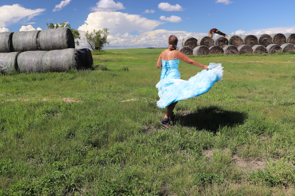 Photograph of Marie LeBlanc dancing and holding the bottom of her dress so that all the layers of frills are visible. Her back is turned to the viewer. Marie is in a grassy field with haybales in the upper left and right of the image. Two trees can be seen on the left and part of some farming equipment can be seen behind the haybales on the right. The sky is blue with lots of white clouds. Marie is a thin white woman with straight long brown hair and is wearing a blue strapless dress with lots of frills at the bottom.