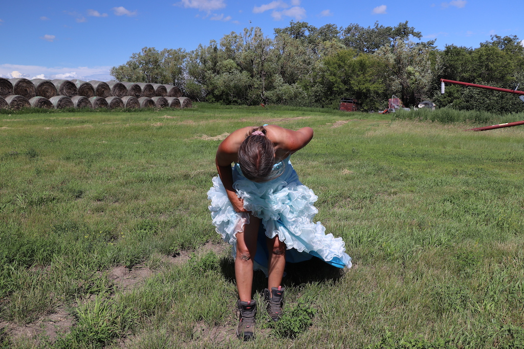 Photograph of Marie LeBlanc bowing to the viewer and holding the bottom of her dress so that her muddy knees are visible. Marie is in a grassy field with haybales in the upper left of the image and trees in the upper right with some farming equipment. The sky is blue with a few white clouds. Marie is a thin white woman with straight long brown hair and is wearing a blue strapless dress with lots of frills at the bottom and work boots.