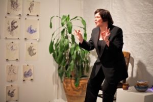 Photo of Andrea von Wichert. Andrea is a white woman with shoulder length born hair. she is wearing a black blazer with a black shirt underneath and black pants. Andrea appears to be speaking and gesturing with her hands. Behind her is artwork on the left wall and a large planted pot behind her