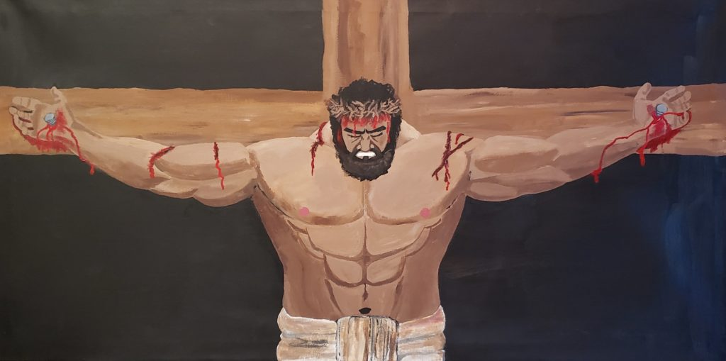 Acrylic painting of Jesus Christ on the cross. In this depiction, Jesus is very well muscled with olive coloured skin, dark brown hair and a full dark brown beard. He is wearing a loin cloth which you can just see at the bottom of the image. His hands are nailed to the cross and he has thorns which are pushed into his head to form a crown. There is blood flowing from his hands, his forehead and on cuts along his arms from being whipped before being nailed to the cross. The background is black.