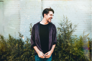 Photo of Nic Dyson. Nic is a white man with short brown hair and short facial hair. Nic is looking to the right and smiling. He is wearing an open purple button up shirt with a black t-shirt underneath and jeans. Nic is standing in front of a grey bricked building with bushes.