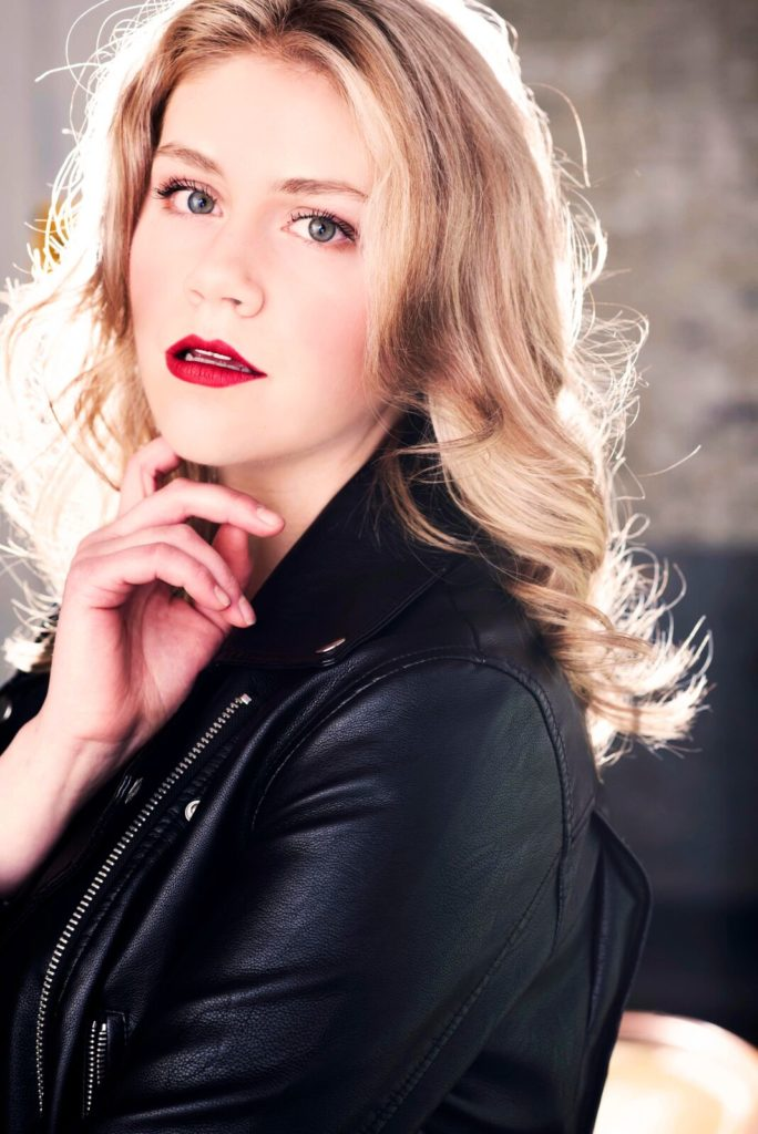 Headshot of Sarah Luby who is a white woman with longblond/light brown wavy hair. She is wearing a black leather jacket and hasbrightred lips and grey/green eyes. She is lookingdirectly at the camera and has herhand under her chin and her mouth is slightly open.