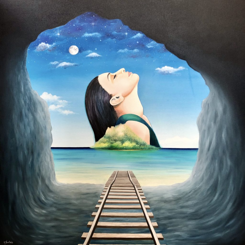 Image description: Surreal painting of an island with a woman rising out of it, viewed through a cave. The cave is dark smooth stone and a wooden train track goes from the cave into the water at the mouth of the cave. The water is light blue and sandy near the cave. The island is floating on the horizon, a third from the bottom of the image. The island consists of a small sandy beach and lush, blurry green flora. Out of the island and behind of it a large image of a woman from the shoulders up is seen. Her head is as large as the island. The woman is white with long straight black hair, pink lips and closed eyes. She wears a green tank top. Her head is thrown back with her hair falling down her back and her face up. The sky behind the woman goes from light white at the horizon, light blue sky and clouds half way up and a dark sky with stars and the moon at the top of the image.