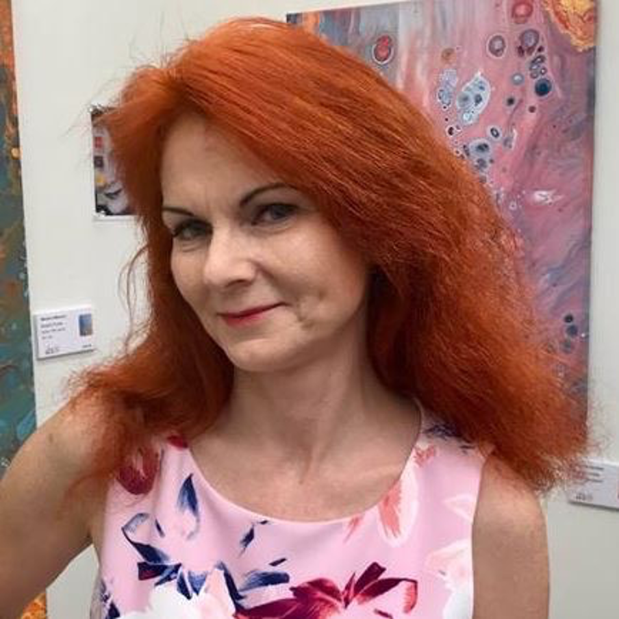 Headshot of Margaret Switala. Margaret us a white woman with red hair. She is smiling in the photo and is wearing a light pink top with flowers. Behind her I s white wall with artwork.
