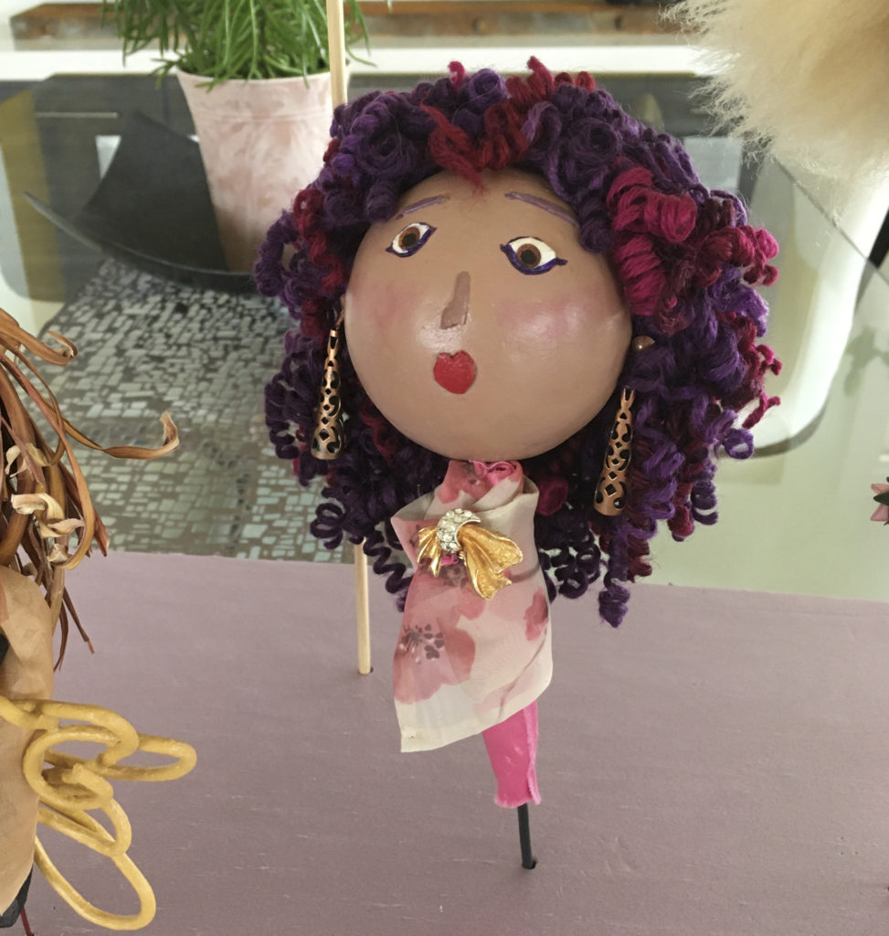 Photograph of a doll sculpture. The doll has light mocha skin, a small red mouth shaped like a heart, pink cheeks and brown eyes. Her hair is purple and pink curls and she has long bronze cut-out earrings. She is wearing a tight pink dress with a cream wrap with pink flowers. She is wearing a pin with gold and glass that looks like diamonds