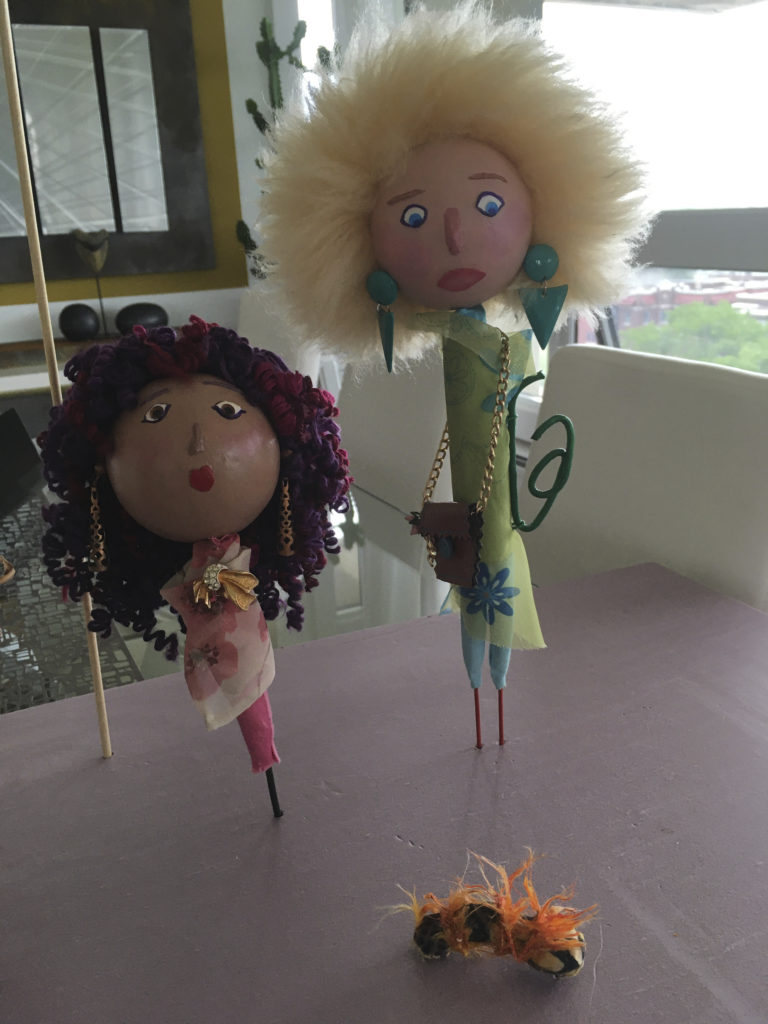Photograph of two doll sculptures looking at caterpillar with orange tufts which is on the ground. The doll on the left has light mocha skin, a small red mouth shaped like a heart, pink cheeks and brown eyes. Her hair is purple and pink curls and she had long bronze cut-out earrings. She is wearing a tight pink dress with a cream wrap with pink flowers. She is wearing a gold and glass pin. The doll on the right is taller than the other and has fluffy blond hair. She has a pink mouth shaped like an oval, pink cheeks and blue eyes. The doll has a slightly confused look on her face. She is wearing dangly green earrings, a green and blue wrapped top and blue tights. The doll also has a leather purse with a gold chain and a blue button.