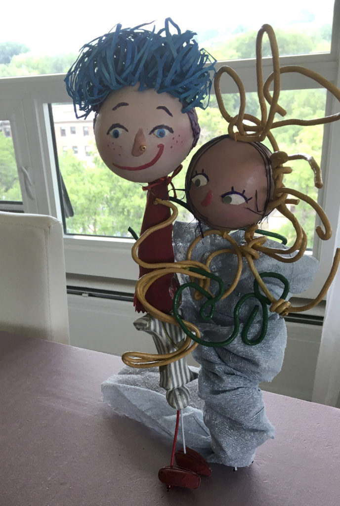 Photograph of two doll sculptures. The doll on the left has white skin, freckles, blue eyes, blue and light purple hair, and a red mouth with a crooked smile. She has a gold bead on her nose and is wearing a red top, striped white and grey bottoms, and red shoes. The baby doll on the right has mocha coloured skin, green eyes, and black wispy hair. She is swaddled in a silvery blue blanket that is wrapped around her like a tornado. There are yellow coated and green coated wire that is wrapped around both of them.