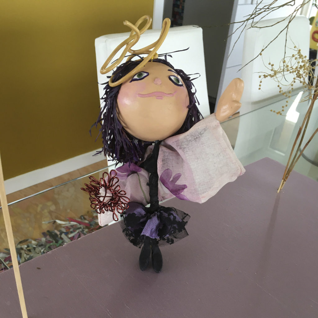 Photograph of a doll sculpture. The doll has Asian skin tone, pink cheeks and lips, and green eyes. Her hair is dark purple Raffia and is made from the segments of the leaves on the Palmyra palm, a tree native to Madagascar . She is wearing a black dress with a purple and black lace skirt. She is also wearing a light pink shawl with purple flowers. She has a yellow twisted wire on her head and is holding flower that is created by twisting reddish coated aluminum wire. The doll has one hand in the air and is looking upwards.