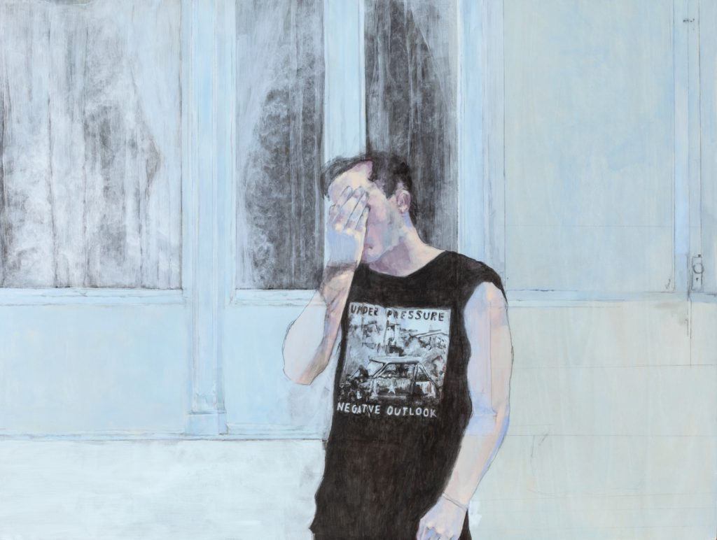 """Painting of a man holding his face in front of a building that is blue and faded. He has white skin, short black hair and is wearing a t-shirt with an image of a car crash with the words """"under pressure"""" above and """"negative outlook"""" below."""