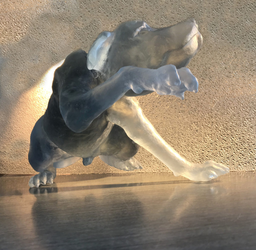 Cast glass dog. The glass is pale blue and translucent. The dog is standing on three legs with one reached out in front of him and appears to be begging or afraid. He is a smaller dog with ears that flop to the side slightly.